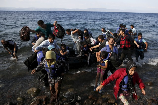 Afghan migrants jump off a dinghy as they arrive on the island of Lesbos, Greece August 23, 2015. Greece, mired in its worst economic crisis in generations, has been found largely unprepared for a mass influx of refugees, mainly Syrians. Arrivals have exceeded 160,000 this year, three times as high as in 2014. The crisis has exposed massive shortages in Greece's available facilities, but also striking discord within the European Union on how to handle the humanitarian crisis. REUTERS/Alkis Konstantinidis